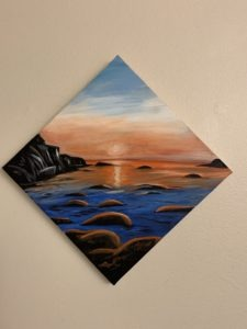 Painting of a sunrise over water with rocks in the foreground. Calm water.